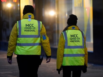 MANCHESTER, ENGLAND - DECEMBER 31: Manchester City Council Covid-19 Marshals patrol the city centre on December 31, 2020 in Manchester, England. New Year's Eve Celebrations have been curtailed in the UK this year dues to Coronavirus pandemic restrictions. With most of the UK in tiers three and four socialising is …