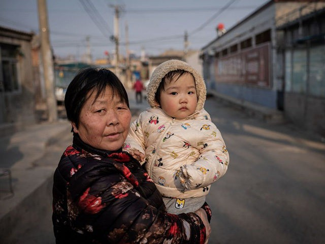 A woman holds a baby on a street in Beijing on February 25, 2021. (Photo by NICOLAS ASFOURI / AFP) (Photo by NICOLAS ASFOURI/AFP via Getty Images)