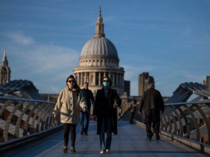 LONDON, ENGLAND - MARCH 16: A woman crosses the millennium bridge in front of St Pauls Cathedral wearing a face mask for protection against the corona virus on March 16, 2020 in London, England. The UK's coronavirus death toll rose to 35 with a total of 1,372 positive tests for …