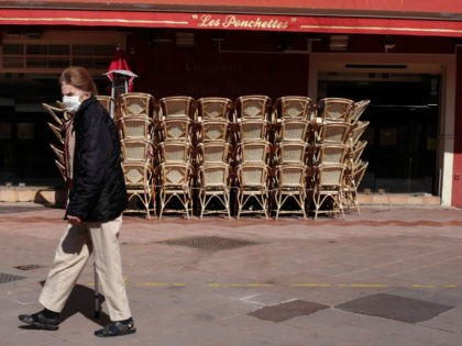 A woman wearing a face mask walks in front of restaurant closed due to the novel coronavirus (COVID-19) on the French Riviera city of Nice, on March 15, 2020. - France on March 14, 2020 drastically stepped up its measures against the spread of the coronavirus, announcing the closure of …