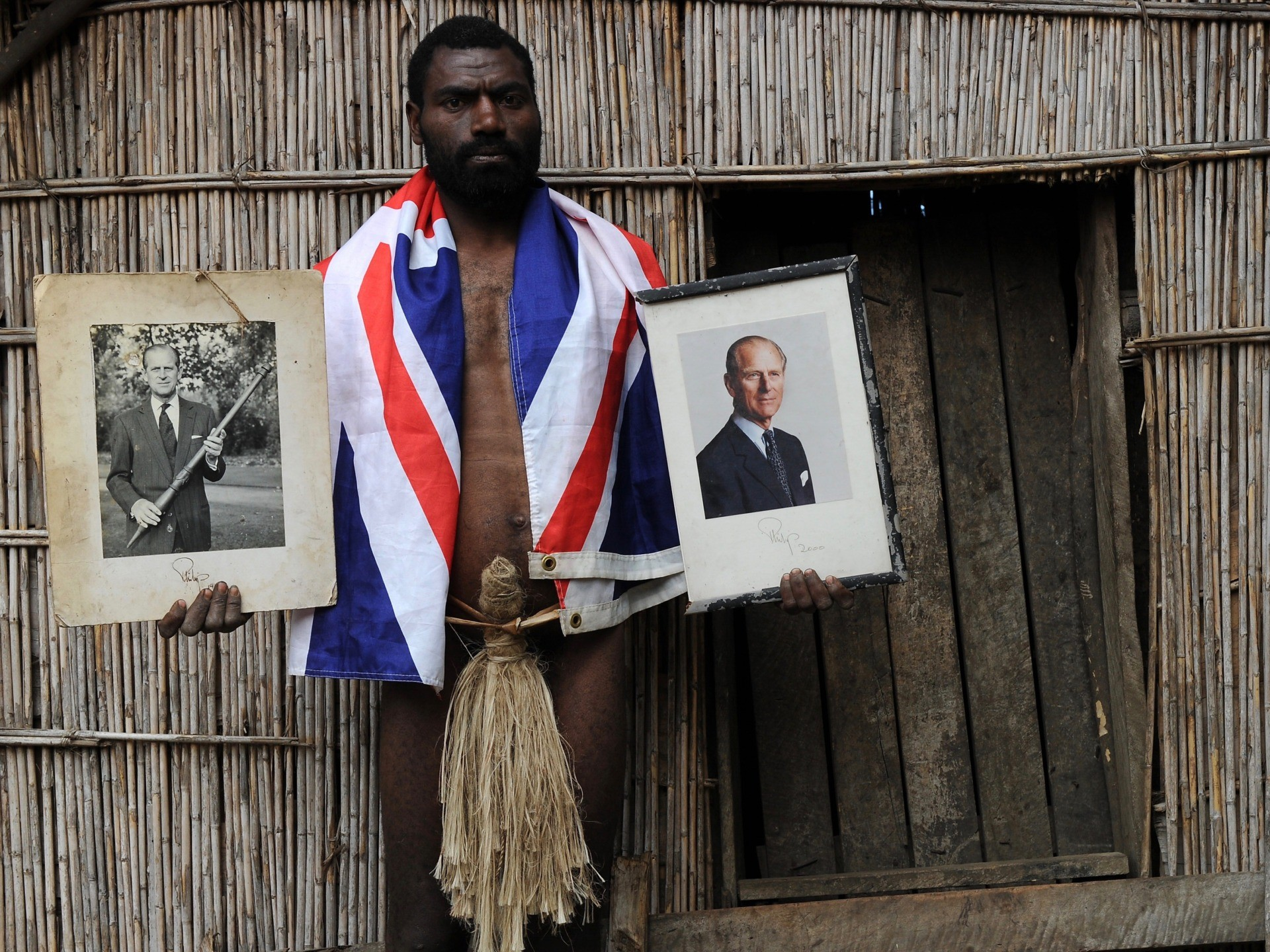 """TO GO WITH AFP STORY """"Vanuatu-Britain-religion-royals,FEATURE"""" by Madeleine Coorey Sikor Natuan, the son of the local chief, holds two official portraits (one holding a pig-killing club, L) of Britain's Prince Philip in front of the chief's hut in the remote village of Yaohnanen on Tanna in Vanuatu on August 6, 2010. In his remote village in Vanuatu, tribesman Sikor Natuan cradles a faded portrait of Britain's Prince Philip against his naked and tattooed chest. Natuan, who just weeks before danced and feasted to mark the royal's 89th birthday, is already preparing for next year's celebrations -- and he is expecting the guest of honour to attend, despite his advanced age. For in the South Pacific village of Yaohnanen on Vanuatu's Tanna island, where men wear nothing but grass penis sheaths, and marijuana and tobacco grow wild, Prince Philip is worshipped as a god. AFP PHOTO / Torsten BLACKWOOD (Photo credit should read TORSTEN BLACKWOOD/AFP via Getty Images)"""