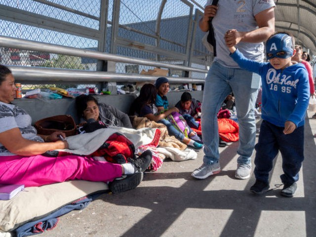 "People walk past migrants camped out waiting to declare asylum on the Paso Del Norte Bridge on November 4, 2018 in El Paso, Texas. - Sending thousands of troops to the US-Mexico border to counter a migrant ""invasion,"" questioning the validity of birthright citizenship, and spreading stories of scandalous murders …"