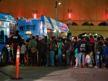 Asylum seekers board a bus stop after they were dropped off by Immigration and Customs Enforcement (ICE) officials earlier at the Greyhound bus station in downtown El Paso, Texas late on December 23, 2018. - The group of around 200, mostly made up of Central Americans, were left without money, …
