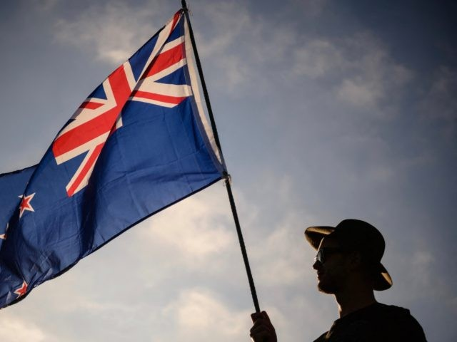 A man raises a New Zealand flag as he attends a vigil in memory of the twin mosque massacre victims in Christchurch on March 24, 2019. - New Zealand will hold a national remembrance service for victims of the Christchurch massacre on March 29, the government announced, as the country …