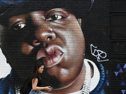 A woman passes by a mural by Brazilian artist Sipros of the rapper Biggie Smalls on a wall in the Bishwick section of Brooklyn, New York on June 6, 2019. - The rapper, died in 1997, and his real name was Christopher George Latore Wallace, known professionally as The Notorious …