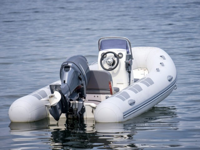 Inflatable White Motor Boat Floating At Sea