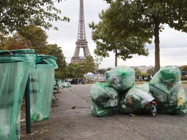 """This picture taken on September 22, 2019 shows piles of garbage bags in a street with the Eiffel Tower in the background, in Paris. - In an article in Britain's Observer newspaper on September 22, 2019, headlined """" Paris, city of romance, rues new image as the dirty man of …"""