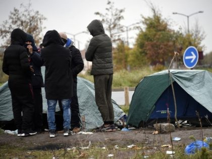 Migrants talk as they stand in front of their makeshift tents set up at the camp in Calais, northern France, on November 15, 2019. (Photo by FRANCOIS LO PRESTI / AFP) (Photo by FRANCOIS LO PRESTI/AFP via Getty Images)