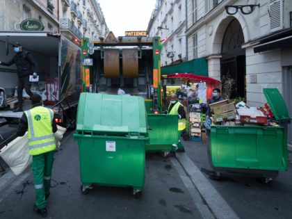 "Rubbish collectors of the Paris municipality cleaning service ""Proprete de Paris"", wearing face masks, collect waste bins to be emptied in a garbage truck in Paris on April 30 , 2020 as France is under lockdown to stop the spread of the COVID-19 pandemic, caused by the novel coronavirus. (Photo …"