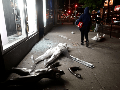Looters walk next to a smashed store in Lower Manhattan on June 1, 2020, after a after demonstrations over the death of George Floyd by a Minneapolis police officer on June 1, 2020 in New York. - New York's mayor Bill de Blasio today declared a city curfew from 11:00 …