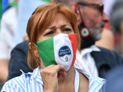 """A woman wearing aface mask in the colors of the Italian flag, reading """"Brothers of Italy"""" attends a united rally of the League (Lega) party, the Brothers of Italy (FdI) party and the Forza Italia (FI) party for a protest against the government on July 4, 2020 on Piazza del …"""