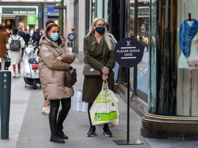 People queue outside shops wearing protective face masks as a precaution against the transmission of the novel coronavirus in Dublin on October 21, 2020 as Ireland prepares to enter a second national lockdown to stem the spread of the virus that causes Covid-19. - Millions of people in Ireland were …