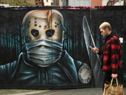 A pedestrian walks by a mural during the national coronavirus restrictions in Manchester, northwest England, on November 26, 2020. - London will escape the tightest restrictions once England's national coronavirus lockdown ends next week, the government said Thursday, but major cities including Manchester and Birmingham face at least two more …
