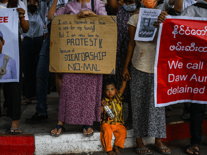 A child looks on as protesters hold signs during a protest against the military coup in Yangon on February 11, 2021. (Photo by Ye Aung THU / AFP) (Photo by YE AUNG THU/AFP via Getty Images)