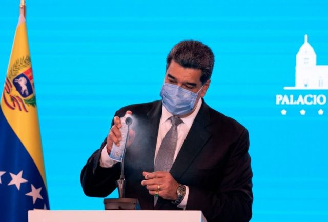 Venezuelan President Nicolas Maduro disinfects a microphone before offering a press conference at Miraflores Presidential Palace in Caracas on February 17, 2021. - Venezuela will start its vaccination campaign against COVID-19 on February 18, after the arrival of the first 100,000 doses of Russian Sputnik V vaccines, including in this …