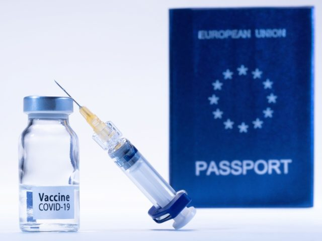 """A picture taken on March 3, 2021 in Paris shows a vaccine vial reading """"Covid-19 vaccine"""" and a syringe next to an European passport. (Photo by JOEL SAGET / AFP) (Photo by JOEL SAGET/AFP via Getty Images)"""