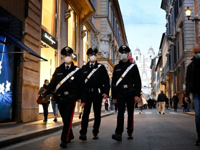 """Carabinieri police officers walk across the Via dei Condotti luxury shopping street in downtown Rome on March 13, 2021 before the government tightens restrictions across most of the country from March 15, facing a """"new wave"""" after it recorded almost 26,000 new Covid-19 cases and another 373 deaths on March …"""