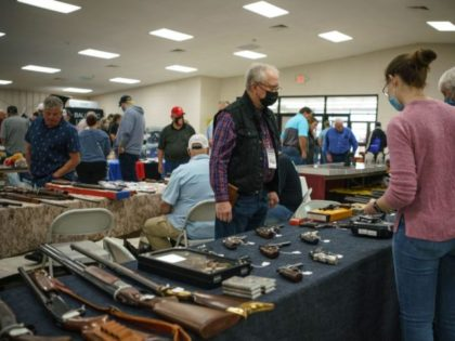 Attendees visit gun show at the 2021 Rattlesnake Roundup at the Nolan County Coliseum in Sweetwater, Texas on March 13, 2021. - The town of Sweetwater holds the largest rattlesnake roundup in the world, launched in 1958 with the sole purpose of getting rid of rattlesnakes, killing an average of …