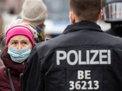 A woman protesting against anti-Coronavirus measures confronts a police officer during a protest in Berlin on March 28, 2021, amid a Coronavirus (Covid-19) pandemic. (Photo by John MACDOUGALL / AFP) (Photo by JOHN MACDOUGALL/AFP via Getty Images)