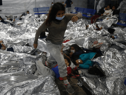 A young female minor walks over others as they lie inside a pod for females at the Donna Department of Homeland Security holding facility, the main detention center for unaccompanied children in the Rio Grande Valley run by the US Customs and Border Protection, (CBP), in Donna, Texas on March …