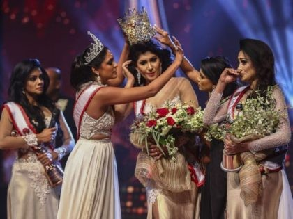 In this photograph taken on April 4, 2021, winner of Mrs. Sri Lanka 2020 Caroline Jurie (2-L) removes the crown of 2021 winner Pushpika de Silva (C) as she is disqualified by the jurie over the accusation of being divorced, at a beauty pageant for married women in Colombo. (Photo …