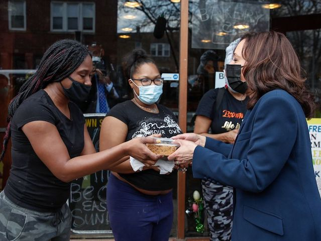 US Vice President Kamala Harris (R) receives a piece of German Chocolate Cake from workers outside of the Brown Sugar Bakery during a quick stop in Chicago, Illinois, on April 6, 2021. - Harris will tour a Covid-19 vaccination site, a partnership between the city of Chicago and the Chicago …