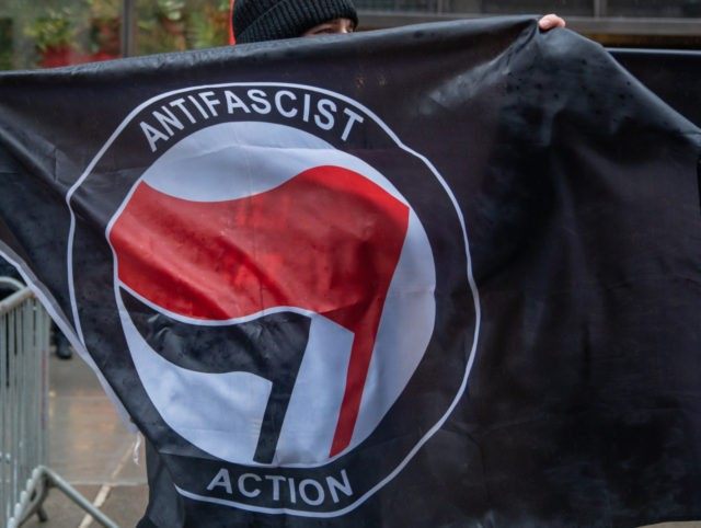 """NEW YORK, NY - APRIL 11: People hold Antifa flags at Trump Tower to counter protest the """"White Lives Matter"""" march and rally on April 11, 2021 in New York City. The march was organized on the encrypted messaging platform Telegram over the last month with a call for nationwide …"""