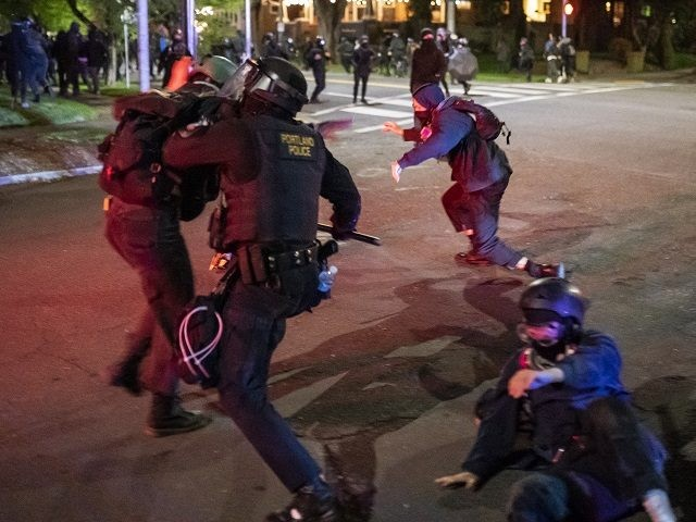 PORTLAND, OR - APRIL 12: A Portland police officers officer tackles demonstrators after a riot was declared during a protest against the killing of Daunte Wright on April 12, 2021 in Portland, Oregon. Wright, a Black man whose car was stopped in Brooklyn Center, Minnesota on Sunday reportedly for an …