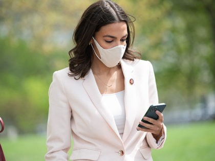 US Representative Alexandria Ocasio-Cortez, Democrat of New York, looks at her cellphone prior to a press conference about a postal banking pilot program outside the US Capitol in Washington, DC, April 15, 2021. (Photo by SAUL LOEB / AFP) (Photo by SAUL LOEB/AFP via Getty Images)