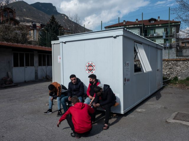 Kurdish migrants smoke cigarettes and wait at the Rifugio Fraternit Massi by Talita Onlus in Oulx, Susa Valley, Alps Region, north-western Italy on April 22, 2021. - A shelter run by an NGO founded by a priest in the Italian Alps has been helping migrants cross into France since 2018. …