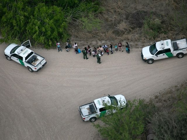 MCALLEN, TEXAS - MARCH 23: U.S. Border Patrol agents take asylum seekers into custody as seen from a Texas Department of Public Safety helicopter near the U.S.-Mexico Border on March 23, 2021 in McAllen, Texas. Texas DPS troopers are taking part in Operation Lone Star in supporting U.S. Border Patrol …