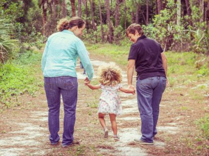 Lesbian couple and their little girl on a walk in a nature area