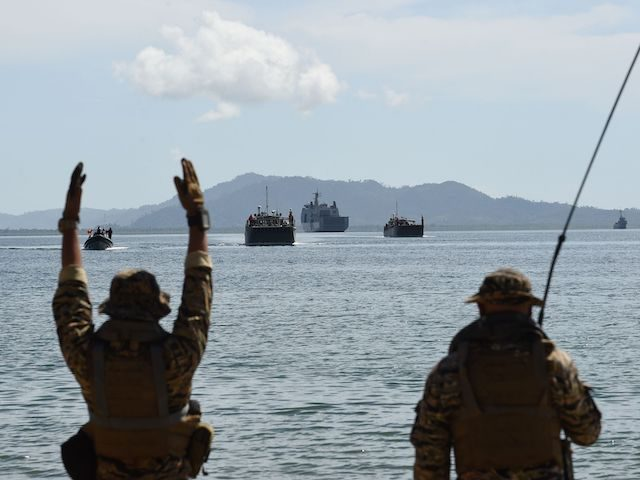 Members of Philippine navy special operations group (NAVSOG) signal to Philippine landing ships loaded with Philippine-US marines, and civilian volunteers as security and disaster responders during a simulation of a disaster drill as part of the annual joint Philippines-US military exercise in Casiguran town, Aurora province on May 15, 2017. …