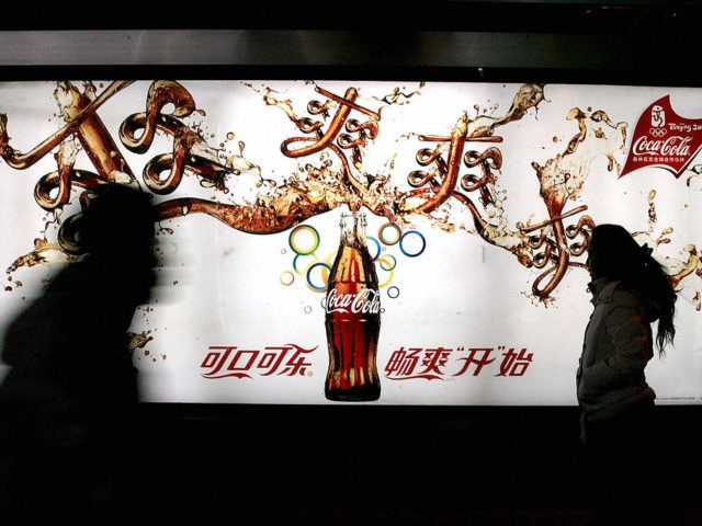 Passersby walk past a new Coca-cola advertisement billboard in Beijing, 09 December 2007. The Coca-Cola Company, the world's largest beverages producer, recently launched a research centre for traditional Chinese medicine in Beijing to develop beverages using Chinese herbal ingredients and formulas. AFP PHOTO (Photo credit should read AFP/AFP via Getty …