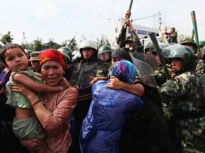 URUMQI, CHINA - JULY 07: Chinese policemen push Uighur women who are protesting at a street on July 7, 2009 in Urumqi, the capital of Xinjiang Uighur autonomous region, China. Hundreds of Uighur people have taken to the streets protesting after their relatives were detained by authorities after Sunday's protest. …