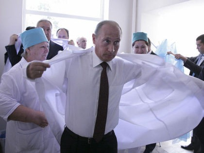 Russian Prime Minister Vladimir Putin puts on a white laboratory coat at a hospital during a visit to the capital of Georgia's breakaway Abkhazia region, Sukhumi on August 12, 2009. Putin pledged Russia's military backing for Abkhazia in any new conflict with Georgia, as he visited the rebel Georgian region …
