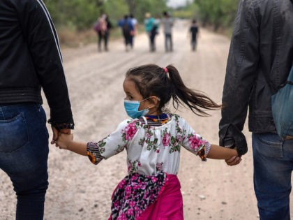 LA JOYA, TEXAS - APRIL 14: An immigrant child glances back towards Mexico after crossing the border into the United States on April 14, 2021 in La Joya, Texas. Many Central American families who make the arduous journey describe their voyage as harrowing though the length of Mexico. Most pay …