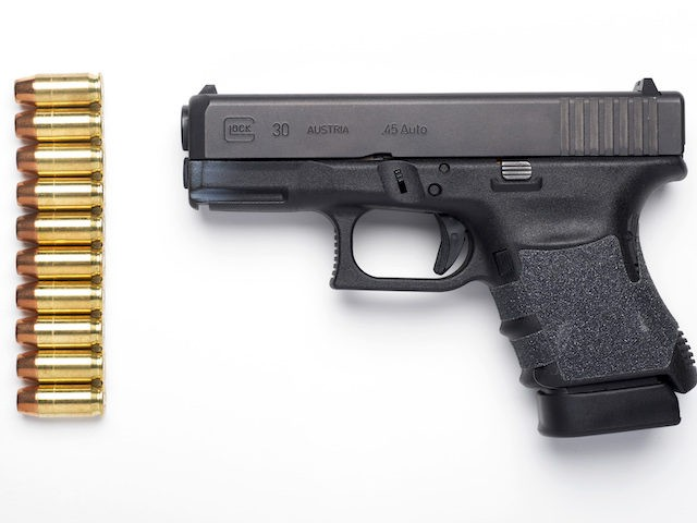 A Glock 30SF .45 Auto semi-automatic pistol with it's standard ten-round magazine installed, and ten rounds of hollow-point ammunition are seen in Alexandria, Va., Wednesday, Feb. 10, 2016. (AP Photo/Cliff Owen)