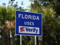 Exclusive — Gov. Ron DeSantis Hangs 'Florida Uses E-Verify' Signs on All Highways into Sunshine State