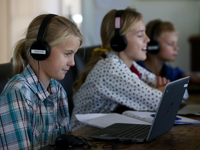 "Alessia Bowman, 10, Sybella Bowman, 12, and Oliver Bowman, 8, do school work at their family home and cattle property on April 05, 2020 in Tarpoly Creek, Australia. Emily Bowman, mother of three, believes the current internet situation highlights ""the great divide between city and country."" She is currently paying …"