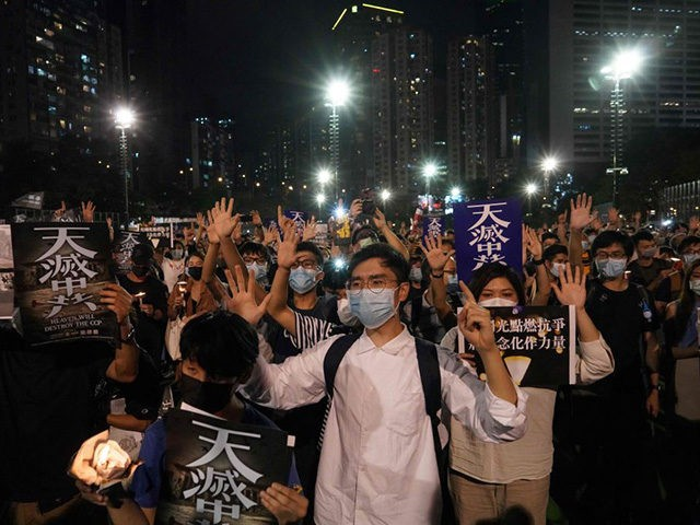 People gesture the popular protest slogan 'Five demands, not one less' as they attend a vigil in Victoria Park in Hong Kong on June 4, 2020, after the annual remembrance that traditionally takes place in the park to mark the 1989 Tiananmen Square crackdown was banned on public health grounds …