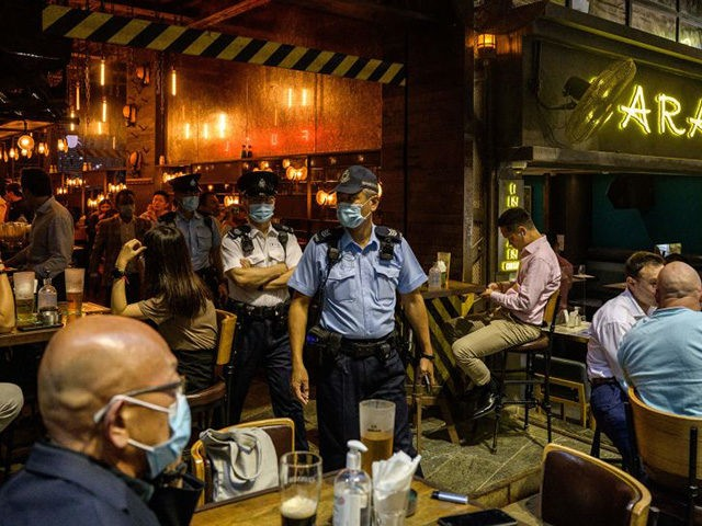 Food and Environmental Hygiene Department officers and police leave after inspecting the license of a restaurant and bar after it reopened, in Lan Kwai Fong, a popular drinking area in Hong Kong on April 29, 2021, as Covid-19 coronavirus social-distancing restrictions on restaurants and bars were eased under new vaccine …