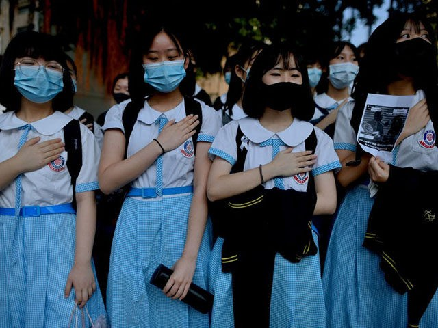 TOPSHOT - Schoolmates of form five student Tsang Chi-kin, 18, who was shot in the chest by police during violent pro-democracy protests that coincided with China's October 1 National Day, place their hands on their chests during a protest at a school in Hong Kong on October 2, 2019. - …