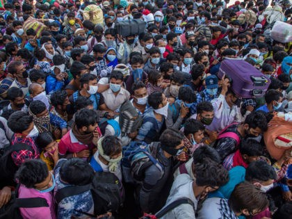 NEW DELHI, INDIA - MARCH 29: Indian migrant workers and labourers along with their families stuck in the national capital, with and without protective masks crowd to board buses to return to their native villages, as nationwide lockdown continues over the highly contagious coronavirus (COVID-19) on March 29, 2020 in …