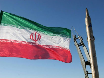 An Iranian flag flutters next to a ground-to-ground Sajil missile before being launched at an undisclosed location in Iran on November 12, 2008. Iran test fired today a new generation of ground-to-ground missile, the semi-official Fars news agency quoted the defence minister as saying. In the past Iran has often …