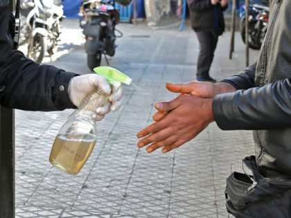 An Iranian man sprays alcohol on the hands of people outside an office building in Tehran on March 4, 2020. - Iran has scrambled to halt the rapid spread of the COVID-19 virus, shutting schools and universities, suspending major cultural and sporting events, and cutting back on work hours. (Photo …