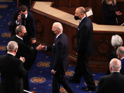WASHINGTON, DC - APRIL 28: U.S. President Joe Biden greets Supreme Court Justice John Roberts with a fist bump before addressing a joint session of congress in the House chamber of the U.S. Capitol April 28, 2021 in Washington, DC. On the eve of his 100th day in office, Biden …