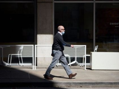 A man with a mask walks through downtown Houston, Texas on March 3, 2021. - Texas Governor Greg Abbott announced he is lifting a mask mandate and that all businesses will be allowed to open at 100% beginning March 10. (Photo by Mark Felix / AFP) (Photo by MARK FELIX/AFP …