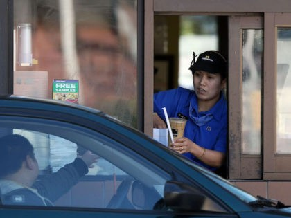SAN FRANCISCO - FEBRUARY 09: A McDonald's drive thru worker hands an order to a customerFebruary 9, 2009 in San Francisco, California. Fast food chain restaurant McDonald's reported a 7.1 percent increase in same store sales for January as people look towards cheaper food alternatives in the weakening economy. (Photo …