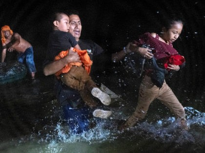 An immigrant father grips his children while walking ashore on the bank of the Rio Grande at the U.S.-Mexico border on April 14, 2021 in Roma, Texas. A smuggler (L), had rafted them over from Mexico with fellow immigrants. A surge of mostly Central American immigrants crossing into the United …